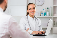 Male visitor consulting smiling woman doctor in hospital Stock Images