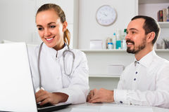 Male visitor consulting smiling woman doctor in hospital. Male visitor consulting smiling positive women doctor in hospital Stock Image