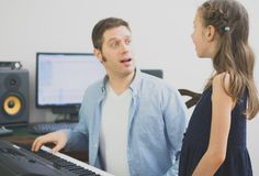 Male vocal coach teaching little girl how to sing. Stock Photo