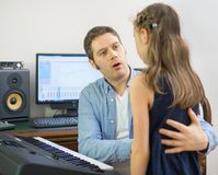 Male vocal coach teaching little girl how to sing. Focused on teacher Stock Images