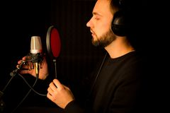 Male vocalist singing into microphone in recording studio. Creating new hit song. Male vocalist singing into microphone in recording studio. Creating new hit Stock Images