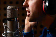 Male Vocalist Singing Into Microphone In Recording Studio. Male Vocalist Sings Into Microphone In Recording Studio Royalty Free Stock Photos