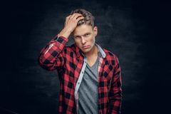 Male vogue model touching his hair. Studio portrait on dark grey background Royalty Free Stock Photo