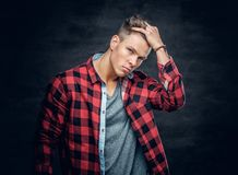 Male vogue model touching his hair. Studio portrait on dark grey background Stock Photos