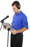 Male Voice Over Artist or Singer. On a microsphone wearing a blue shirt on a white background Royalty Free Stock Images