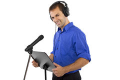 Male Voice Over Artist or Singer. On a microsphone wearing a blue shirt on a white background Stock Photo