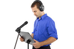 Male Voice Over Artist or Singer. On a microsphone wearing a blue shirt on a white background Stock Image