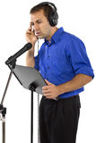 Male Voice Over Artist or Singer. On a microsphone wearing a blue shirt on a white background Stock Images