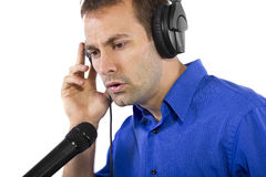 Male Voice Over Artist or Singer. On a microsphone wearing a blue shirt on a white background Royalty Free Stock Photography