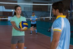 Male volleyball player practicing with coach. Young male volleyball player practicing with coach at court Stock Photo