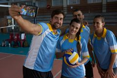 Male volleyball player with team taking selfie. Happy male volleyball player with team taking selfie at court Royalty Free Stock Photography