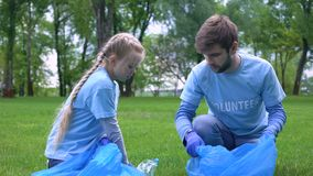 Male volunteer and daughter collecting garbage forest together, giving high five. Stock footage stock footage