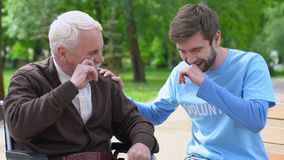 Male volunteer and elderly disabled man laughing in park, lonely pensioners care