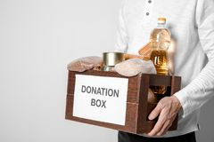 Male volunteer holding donating box. With food against white background Royalty Free Stock Images
