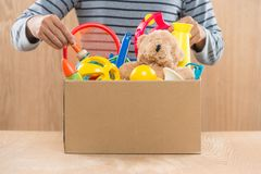 Male volunteer holding donation box with old toys. Stock Photography