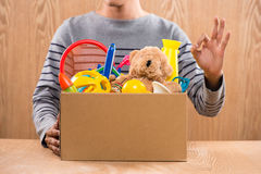 Male volunteer holding donation box with old toys. Royalty Free Stock Image
