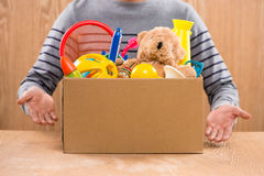 Male volunteer holding donation box with old toys. Stock Photos