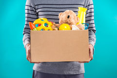 Male volunteer holding donation box with old toys. Royalty Free Stock Photos