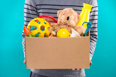 Male volunteer holding donation box with old toys. Royalty Free Stock Photo