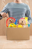 Male volunteer holding donation box with old toys. Royalty Free Stock Images