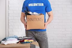 Male volunteer holding donation box with shoes. Indoors Stock Photography