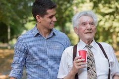 Male volunteer supporting old man. Photo of handsome male volunteer supporting old man Royalty Free Stock Images