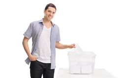 Male voter casting a vote into a ballot box Royalty Free Stock Image