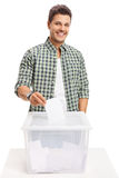 Male voter casting a vote into a ballot box Royalty Free Stock Photo