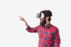 Male in VR glasses pointing away. Side view of bearded man in checkered shirt and VR headset pointing away on white background Royalty Free Stock Image