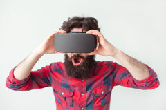 Male in VR glasses. Young bearded man in checkered shirt and VR headset looking impressed on white background Royalty Free Stock Images