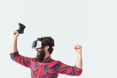 Male in VR headset winning. Young bearded man wearing VR headset and holding hands up in gesture of victory Stock Images