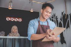Male waiter in apron writing order. Happy asian male waiter in apron writing order Stock Photo