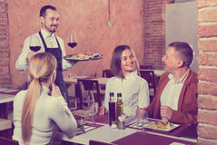 Male waiter bringing order to visitors Royalty Free Stock Images