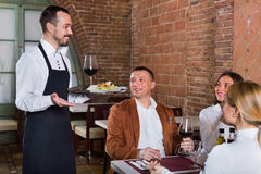 Male waiter bringing order to visitors Royalty Free Stock Photography