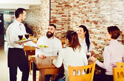 Male waiter carrying order for visitors in country restaurant Royalty Free Stock Images