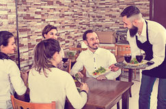 Male waiter carrying order for visitors in country restaurant Royalty Free Stock Photography