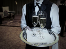 Male waiter with champagne flutes. Waiter welcomes guests with champagne Stock Photos
