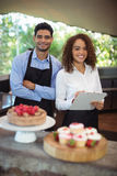 Male waiter and female waitress with clipboard. At outdoor restaurant Stock Images