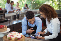 Male waiter and female waitress with digital tablet. At outdoor restaurant Stock Image