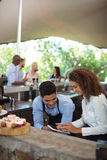 Male waiter and female waitress with digital tablet. At outdoor restaurant Royalty Free Stock Photos