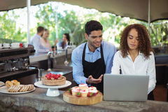 Male waiter and female waitress with laptop. At outdoor restaurant Royalty Free Stock Photo