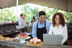 Male waiter and female waitress with laptop. At outdoor restaurant Royalty Free Stock Photos