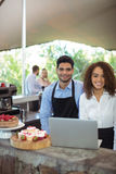 Male waiter and female waitress with laptop. At outdoor restaurant Royalty Free Stock Images