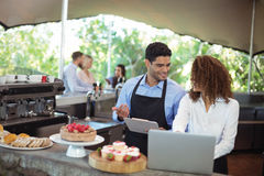 Male waiter and female waitress with laptop. At outdoor restaurant Stock Photos