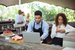 Male waiter and female waitress with laptop. At outdoor restaurant Royalty Free Stock Photography