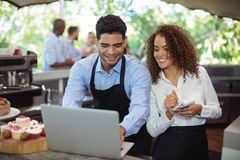 Male waiter and female waitress with laptop. At outdoor restaurant Stock Photo