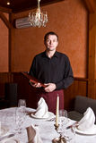 Male waiter with the folder menu at the hands. Of the table in a restaurant Stock Photography