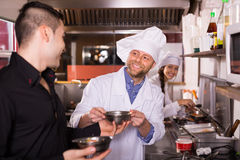 Male waiter holding dishes at kitchen Stock Photography