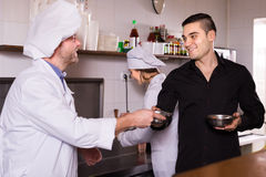 Male waiter holding dishes at kitchen Stock Photo
