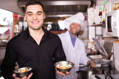 Male waiter holding dishes at kitchen. Smiling male waiter taking away prepared food at bistro kitchen Stock Photos